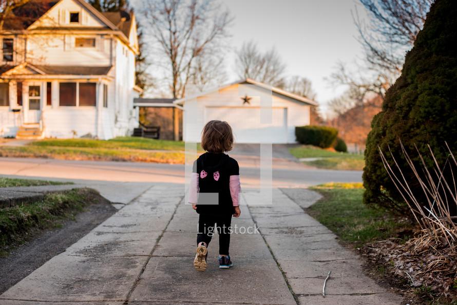 toddler walking on a sidewalk