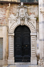 Arched black church doors in stone archway with Catholic emblem over