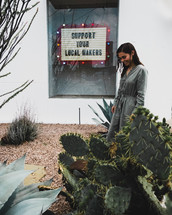 a woman standing on a sidewalk downtown standing in front of a sign that say support your local makers