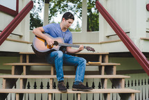 A young man plays a guitar outside in a gazebo rehearsing for worship music.