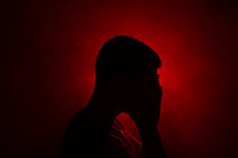 silhouette of a man covered his face
