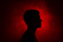silhouette of a man standing in red light