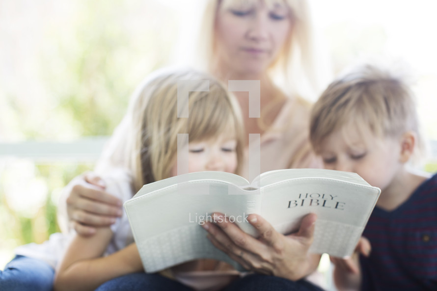 mother reading the Bible to her children