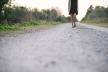 young woman walking down a gravel road