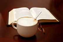 open Bible and coffee on a wood table