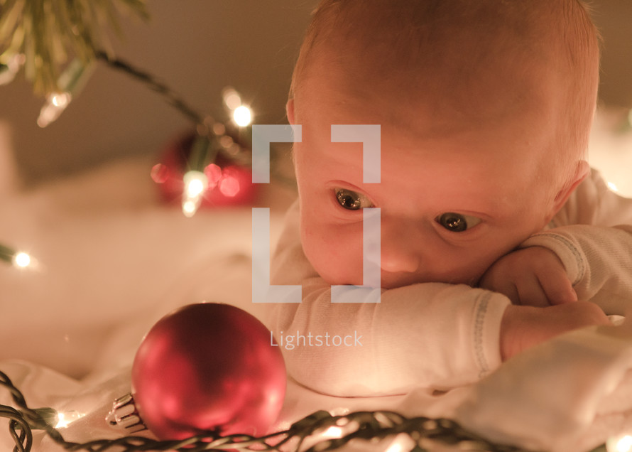 newborn baby and a Christmas ornament