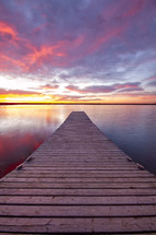 dock over calm water at sunset