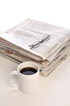 stack of newspapers, coffee mug, and reading glasses