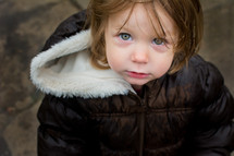 face of a toddler girl in a coat