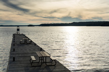 Picnic tables on a wooden pier on a lake.