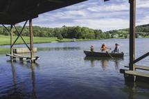 rowing in a fishing boat under a bridge