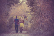 A couple walking holding hands on a nature trail