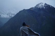 a woman wrapped in a blanket looking out at mountains