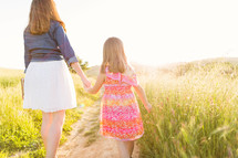 mother and daughter walking holding hands carrying a Bible