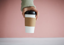 a hand taking a coffee cup