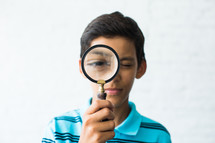 boy child looking through a magnifying glass