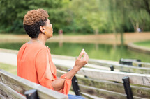 a woman sitting on a park bench with hands raised praying to God