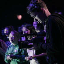 A young man shooting video of a youth worship service.