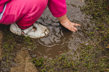 a toddler playing in a mud puddle