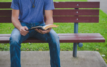 A man reads a Bible on a bench in a park
