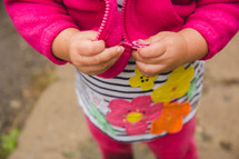 a toddler girl holding the zipper of her jacket
