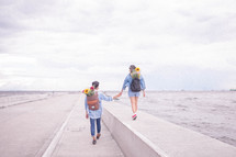 a couple on a date with flowers in their backpacks walking on a bridge over the ocean