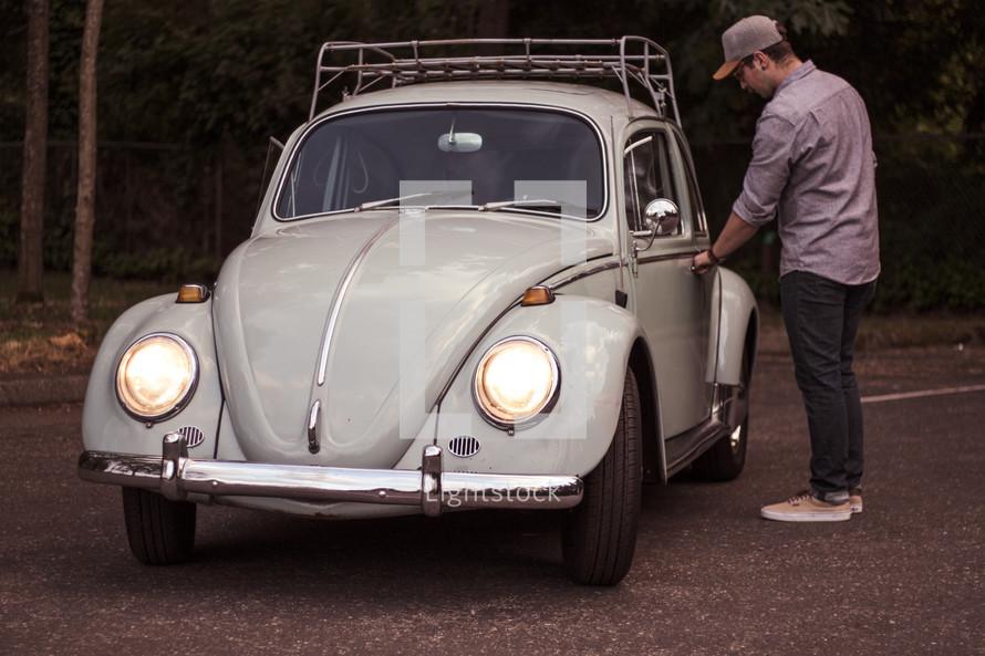 a man opening the door of a vintage Volkswagen Beetle