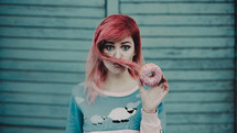 a young woman with pink hair holding a donut