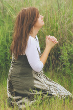 a young woman kneeling in a field praying