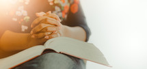 praying hands over a Bible in a woman's lap