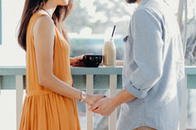 a couple holding hands standing in front of a cafe window