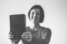 woman holding up a book