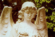 A statue of a guardian angel at a historic grave site looking pensive and thoughtful guarding and standing over a grave. How sober a thought to think about eternity and eternal life when visiting a grave yard or cemetery thinking about loved ones that have gone on before us and hoping to see again one day for all eternity in Heaven with Christ Jesus and the Angelic Heavenly host.