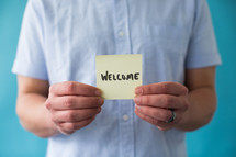 man holding a piece of paper with word welcome