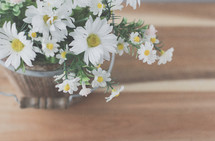 a wooden bucket full of white daisies