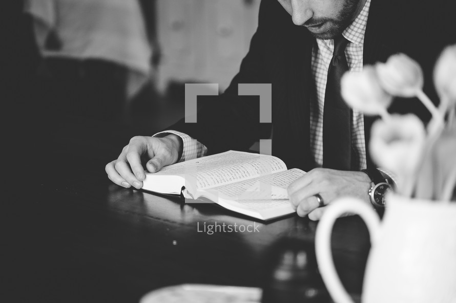 man in a suit sitting at a table reading a Bible