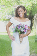 smiling bride holding a bouquet of flowers