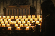 a woman lighting a candle in a cathedral