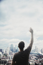 man standing in front of a city with a raised hand