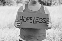 woman holding a sign that reads hopeless
