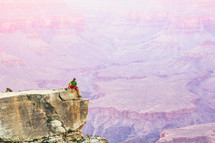 a man sitting at the edge of a cliff overlooking a canyon