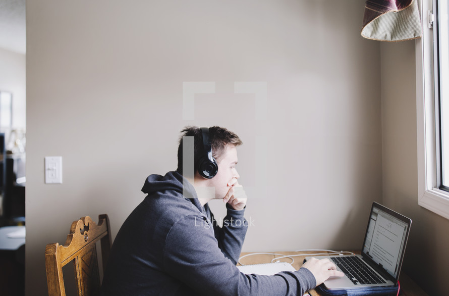 a young man studying on laptop while listening to music