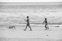 children and a dog walking on a beach