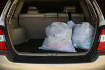 bags of clothes to donate in the back of an SUV