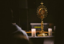 People praying before a Catholic monstrance in Eucharistic adoration