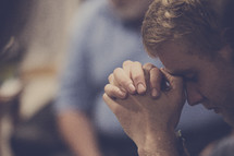 man with head bowed in prayer