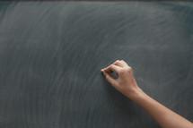 teacher writing on a chalkboard