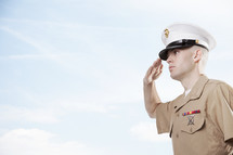 Marine soldier in uniform saluting outside.