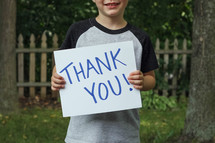 child holding a thank you sign