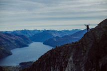 woman standing on a mountaintop with raised hands